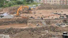 Les constructeurs travaillent au chantier de construction en quelques jours d'été banque de vidéos