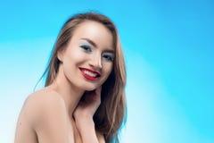 Les contacts de sourire de fille de belles lèvres rouges blondes par les doigts fa image libre de droits