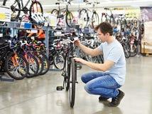Les contrôles d'homme font du vélo avant l'achat dans la boutique de sports Images libres de droits