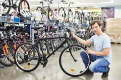 Les contrôles d'homme vont à vélo avant l'achat dans la boutique de sport Photo stock