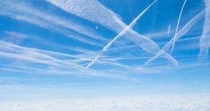 Les Contrails zigzaguent à travers un ciel bleu profond Image stock