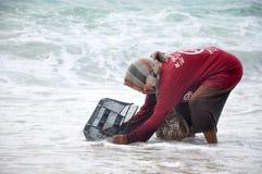 Les coquillages asiatiques pauvres de cueillette de femme sur l'océan étayent un jour orageux La Thaïlande, île de Ko Samui photographie stock