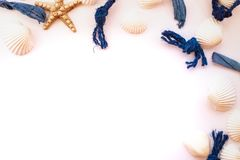 Les coquillages, les cordes de mer et les étoiles de mer ont organisé sur le fond rose Vue de ci-avant Concept tropical de vacanc images stock