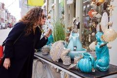 Les coquilles bleues de mer de vase à brune de cheveux bouclés de manteaux en verre de marché en plein air d'achats de jeune femm photos stock