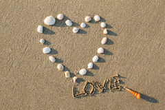 Les coquilles et le dessin en forme de coeur de mer marquent avec des lettres l'amour sur la plage de sable Photographie stock libre de droits