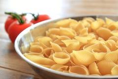 Les coquilles sèches de pâtes de conchiglie dans un acier inoxydable roulent avec des tomates de vigne à l'arrière-plan brouillé Photo stock