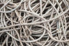 Les cordes grises de mer se situent dans un tas dans le port de pêche Photos libres de droits