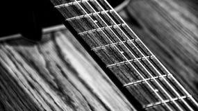 Les cordes noires et blanches de détail de diagonales de ficelles de guitare chantent le jeu de chanson images libres de droits