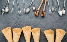 Les cornets de crème glacée plats de configuration collection, cuillères, fourchette et miel plongent Image libre de droits