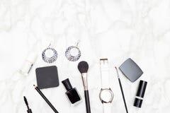 Les cosmétiques et les accessoires femelles sont noirs et blancs sur un marbre Photos libres de droits