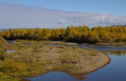 Les couleurs d'automne entourent un lac et des nuages gris ci-dessus Image libre de droits