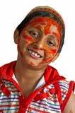 Les couleurs de sourire de Holi de jeune garçon font face au blanc de capuchon Images stock