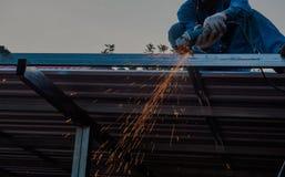 Les coupes metal par le travailleur de sexe masculin avec beaucoup d'étincelles en acier industriel Photos libres de droits