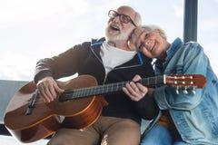 Les couples âgés riants appréciant la chanson ont joué par le mari photographie stock libre de droits
