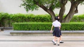 Les couples élevés thaïlandais asiatiques mignons d'étudiante d'écolières dans l'uniforme scolaire ont l'amusement jouant chasser clips vidéos