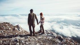 Les couples équipent et femme marchant en montagnes Photographie stock libre de droits