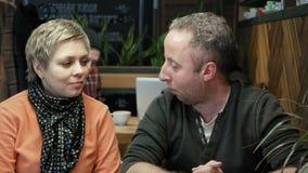 Les couples équipent et la femme mange des entretiens dans le restaurant de café banque de vidéos