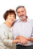 Les couples aînés de sourire se retiennent pour des mains Image stock
