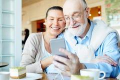 Les couples aînés heureux utilisent l'ordinateur Image stock