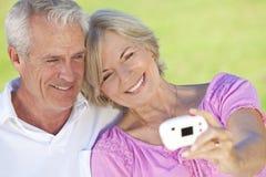 Les couples aînés prennent la photographie sur l'appareil photo numérique Image stock