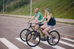 Les couples actifs sur un vélo montent dans la campagne un jour ensoleillé Photographie stock