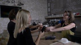 Les couples adolescents dans un café font des emplettes utilisant le smartphone pour payer le café tout en étant amical servi par clips vidéos