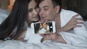 Les couples affectueux dans des manteaux blancs sur le lit font heureusement le selfie sur une vidéo de longueur d'actions de mou clips vidéos