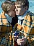 Les couples affectueux dans la couverture en hiver boivent du thé Images libres de droits