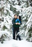 Les couples affectueux heureux marchant dans la forêt neigeuse d'hiver, dépensant Noël vacation ensemble Capture de mode de vie Photographie stock libre de droits