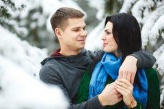 Les couples affectueux heureux marchant dans la forêt neigeuse d'hiver, dépensant Noël vacation ensemble Capture de mode de vie Photo libre de droits