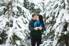 Les couples affectueux heureux marchant dans la forêt neigeuse d'hiver, dépensant Noël vacation ensemble Capture de mode de vie Image stock