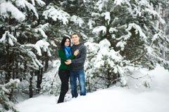 Les couples affectueux heureux marchant dans la forêt neigeuse d'hiver, dépensant Noël vacation ensemble Capture de mode de vie Photo stock