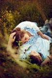 Les couples affectueux se situant dans l'herbe en été mettent en place Photo libre de droits