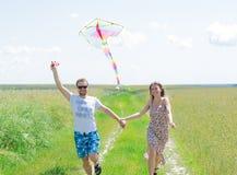 Les couples affectueux sont cerf-volant de fling sur un pré Photographie stock