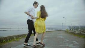 Les couples affectueux sur la berge dansant ensemble Femme dans la robe jaune intéressante banque de vidéos