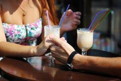 Les couples aiment le café de boissons en café, tenant la main de chacun Images stock