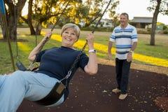 Les couples américains supérieurs heureux environ 70 années appréciant à l'oscillation se garent avec le mari poussant l'épouse s Photos libres de droits