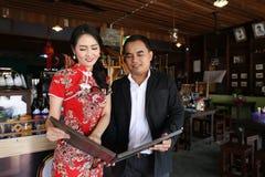 Les couples asiatiques dans le style chinois s'habillent dans un restaurant local Photo stock