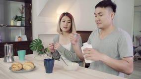 Les couples asiatiques doux heureux prenant le petit déjeuner, céréale en lait, pain et buvant du jus d'orange après se réveillen banque de vidéos