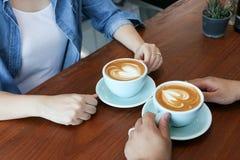 Les couples asiatiques heureux dans la blue-jean ont le café chaud de latte Photo libre de droits
