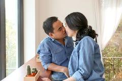 Les couples asiatiques heureux dans la blue-jean s'embrassent dans un café Images libres de droits