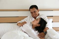 Les couples asiatiques heureux dans la chemise blanche se tiennent sur le lit Image libre de droits