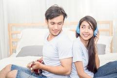 Les couples asiatiques heureux dans le jeune homme d'amour jouant la guitare et chantent la chanson d'amour Photos stock