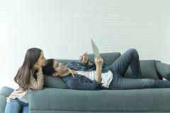 Les couples asiatiques semblent bons sur le sofa Regardez quelque chose par le Th photographie stock libre de droits