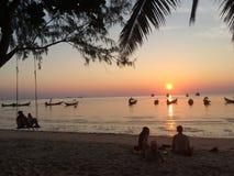 Les couples balancent observant le coucher du soleil, quelques personnes se reposent sur la plage écoutant la musique Image stock