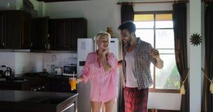 Les couples boivent Juice Dance In Kitchen orange, le jeune homme heureux et la communication de matin de femme en appartement mo clips vidéos