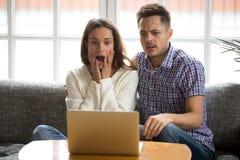 Les couples choqués ont confondu et ont effrayé le film d'horreur de observation sur l'ordinateur portable Images libres de droits