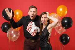 Les couples contrariés dans des vêtements noirs tiennent le boîte-cadeau célébrant la fête de vacances d'anniversaire d'isolement photo stock