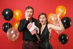 Les couples contrariés dans des vêtements noirs tiennent le boîte-cadeau célébrant la fête de vacances d'anniversaire sur l'air r photographie stock libre de droits