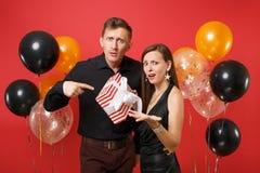 Les couples contrariés dans des vêtements noirs tiennent le boîte-cadeau célébrant la fête de vacances d'anniversaire sur l'air r photos libres de droits